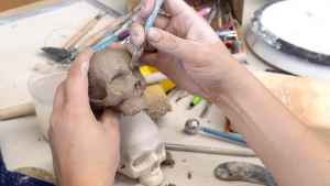 Hands sculpting a clay figure