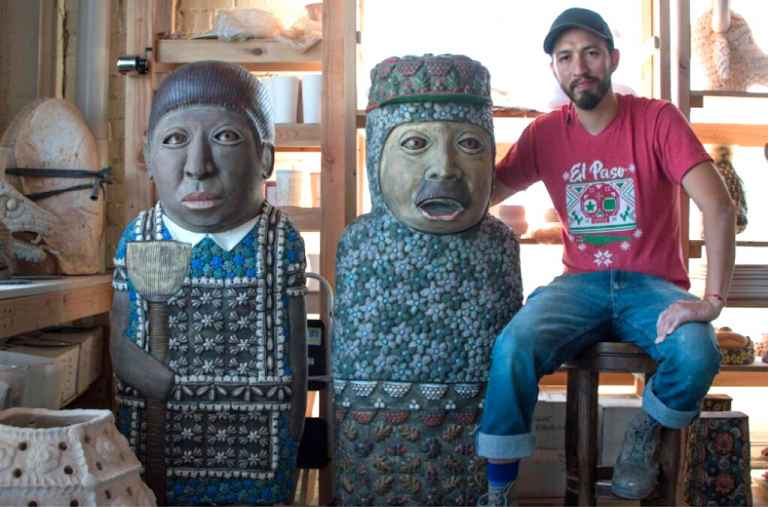 Artist George Rodriquez with two totemic figures